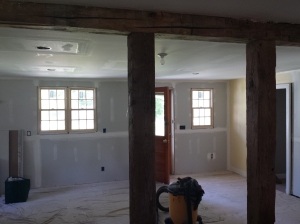 View of new door and windows through beams separating the Kitchen and Dining Room