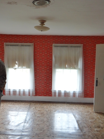 "Bedroom 1: Old linoleum ""rug"" covering wood floors, red eagle wallpaper circa 1940."