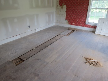 Original wood floors showing patch where stove pipe came up through floor. New wall installed between rooms after door was removed.
